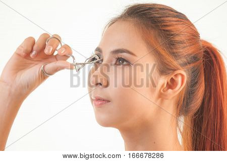 Young asian beautiful girl making her eyelashes wider with curler
