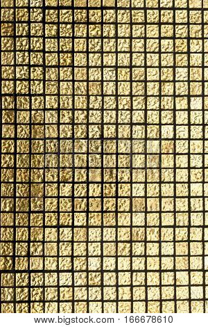 Gold colored tiles of pool walls under the water