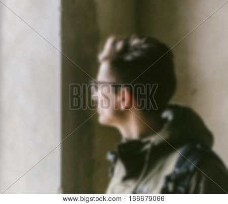 Blurred defocused young man looking through a window