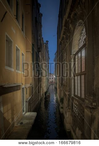 Gondolier in a narrow channel of Venice at night
