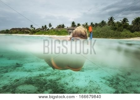 Woman is snorkeing in blue water of Indian ocean