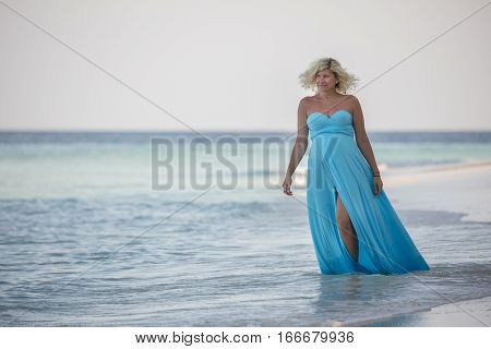 Wonderful pregnant woman is smiling and walking in the sea