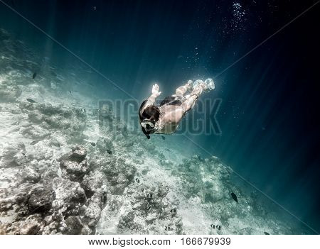 Man is diving to the coral reef in Indian ocean