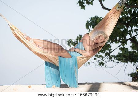 Beautiful blonde girl is lying in hammock