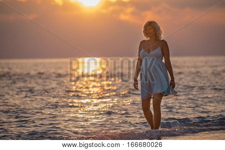 Pregnant beautiful woman is walking on the Maldivian beach during the sunrise