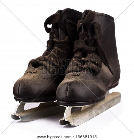 front view of a pair of small children black ice skates covered in dust isolated on white background