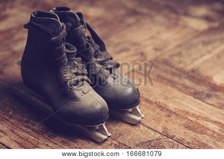 front view of a pair of small children black ice skates covered in dust on wood background