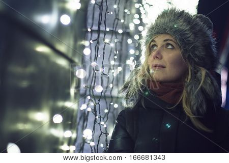 Caucasian blonde woman dressed for winter watching the decorative lled ights on a building wall night city scene