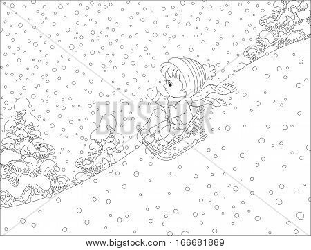 Small child sliding down the snowy hill on a sledge