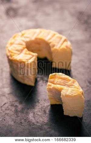 Portion Cut From Whole Golden Camembert Cheese On Dark Tray