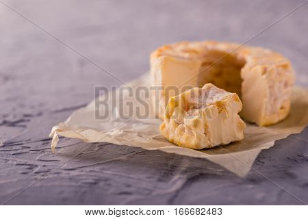 Portion Cut From Whole Golden Camembert On Grey Textured Board