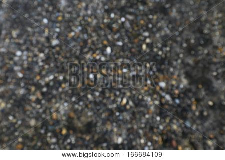 Blurred background motif: small pebbles in dark soil