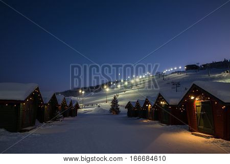 winter market village in Levi, Finland in the evenig on lightened ski cable way background