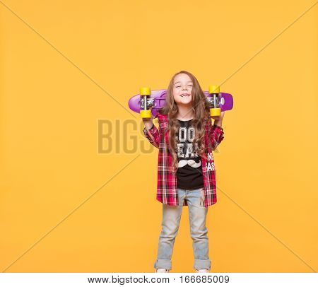 cute little hipster girl holding a skateboard over yellow background. Full length studio portrait of kid in casual street style wear standing cool at color wall