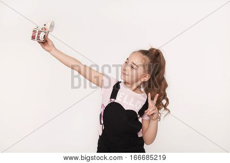 Studio portrait of little girl taking a selfie photo with a retro camera isolated on white background. Kid photographing herself. Children narcissism concept