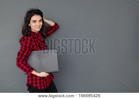 caucasian smiling student girl holding laptop over gray background. Young woman with dark hair wearing casual checked shirt standing at dark wall with copy space