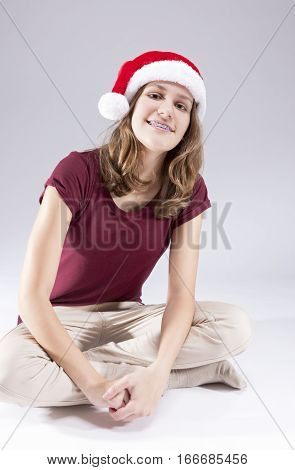 Dental Concepts and Ideas. Happy Caucasian Teenager in Santa Hat With Teeth Brackets. Sitting. Vertical Shot