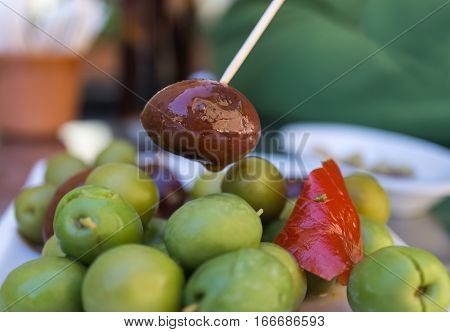 Close-up of Black Olive caught with a toothpick from a spiced olives plate on tapas bar table a typical Spanish black and green split variety in detail, with the red touch of a pepper