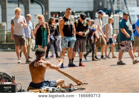 SYDNEY AUSTRALIA - OCTOBER 16 2016: Aborigine man playing a didgeridoo during a music performance near Circular Quay in Sydney harbour.