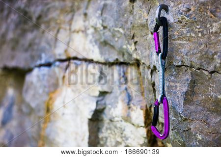 Snap hooks with loop for activity climbing and mountaineering weighs on the rock.