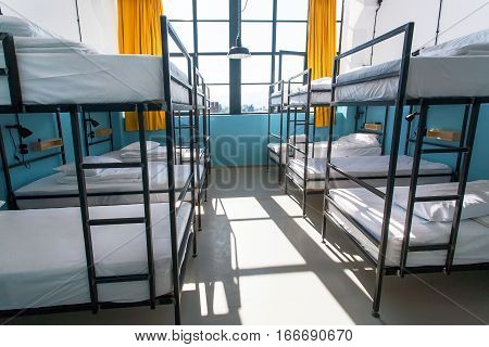 Morning inside the hostel bedroom with clean white beds for students and lonely young tourists.