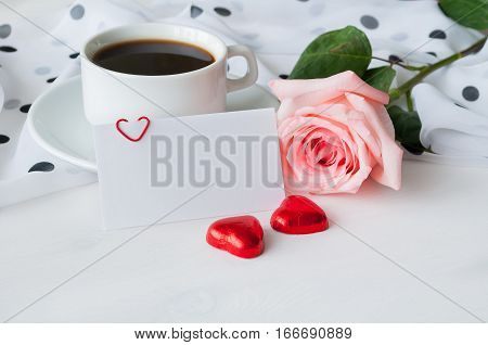 Love background - cup of coffee rose blank love card and two heart shaped candies romantic love still life. Love concept composition