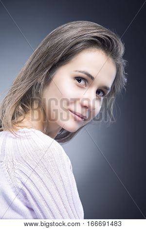 Portrait of Sensual and Shy Positive Caucasian Brunette With Natural Long Hair Posing in Sweater Against Black Background. Vertical Image Orientation