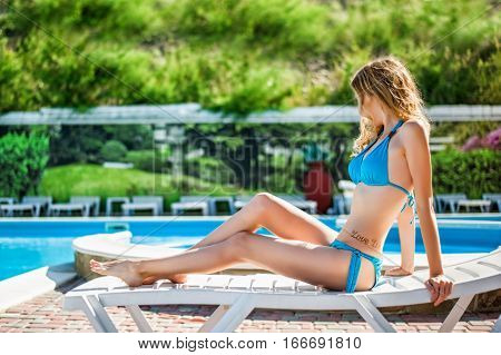 Beautiful slim sexy woman wearing blue bikini relax on beach chaise longue near outdoor water pool. Vacation on resort