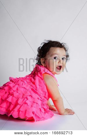 An adorable baby girl sits on a white background and looks back over her shoulder at the camera. She has black curly hair and is wearing a pink frilly dress.