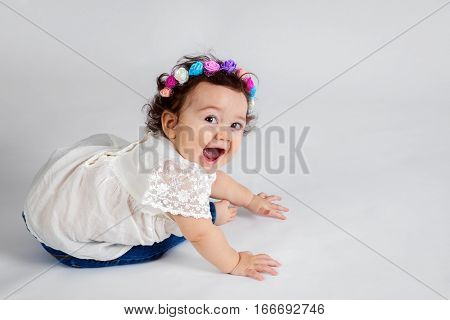 An extremely cute and expressive baby girl turns to look over her shoulder at the camera. She has a floral headband bright eyes and a wide open smiling mouth.