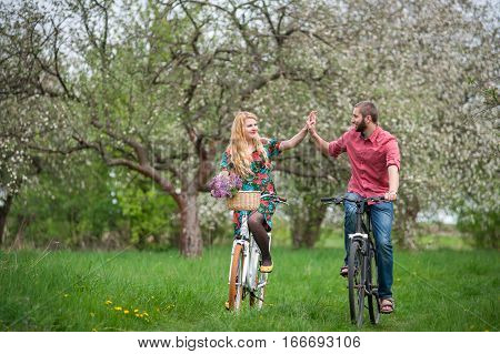 Loving Young Couple Riding Bicycles In The Spring Garden