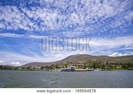 View of the Yahuarcocha lake and instalations, from a boat in the center of the lake, ground view, Ecuador