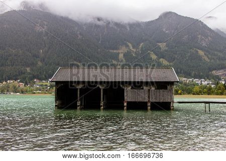 Boatshed on a green lake with mountains, Tirol, Austria.