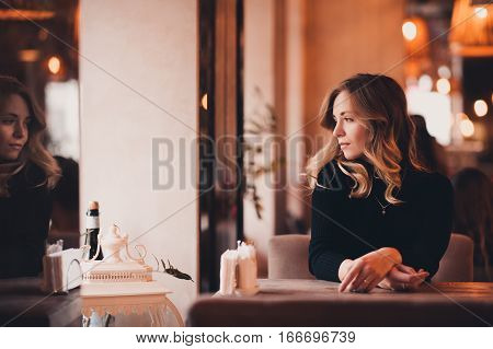Beautiful blonde girl 20-24 year old sitting in cafe looking at window. 20s. Winter season.