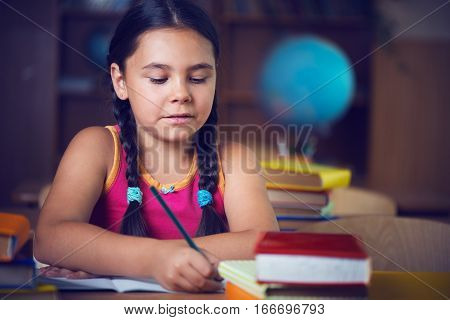 Cute hispanic girl writing in notebook in classroom at school