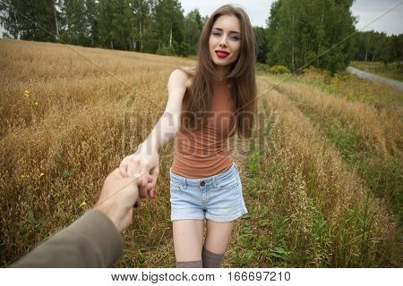 Follow Me. Young happy guy pulls the girls hand
