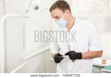 dentist in a medical mask looking looks away, holding a dental pliers