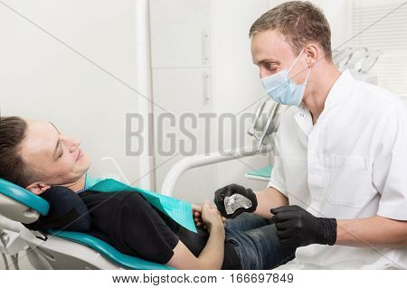 Male dentist looking at patient, holding metal spoon for dental impression, in dental clinic office. stomatology and health care concept