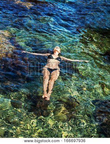 Relaxation in water. Freedom and perfect vacation. Young slim woman lies on surface of transparent seawater
