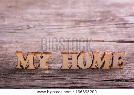 words my home made of wooden letters with a golden key on old boards