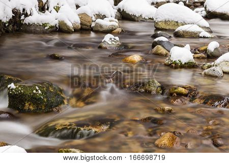 Fast mountain river flowing among stones in winter forest. Beaches and rocks are covered with snow.