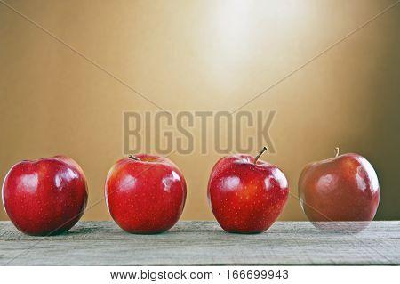 Cztery polskie czerwone jabłka na drewnianym stole