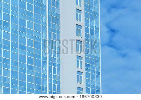 multi-story glass office building against the sky.