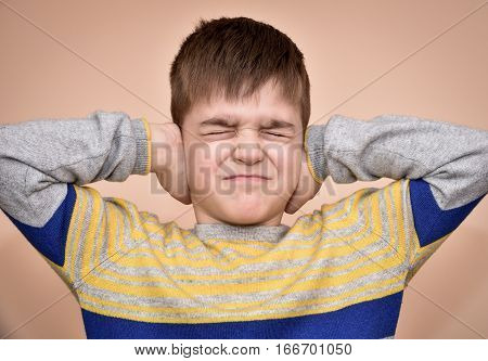 Young boy with closed eyes covering ears with hands