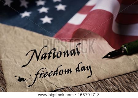 the text national freedom day written in an old piece of paper with a nib pen and a flag of the United States, on a rustic wooden background