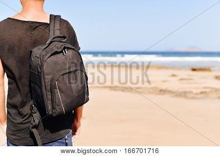 closeup of a young caucasian man seen from behind wearing a t-shirt and carrying a backpack, standing on a white sand beach