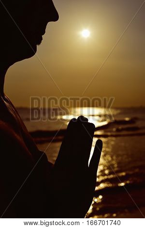 the silhouette of a young man with his hands put together as prying in front of the sea in backlight