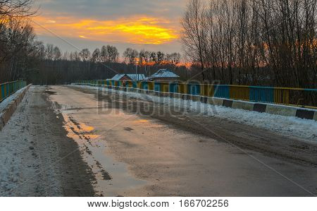 KRASNA LUKA UKRAINE - NOVEMBER 18 2016:Lonely kid back from school to the home at sunset time over empty bridge over Hrun' river near Krasna Luka village in Poltavskaya oblast Ukraine at November 18 2016
