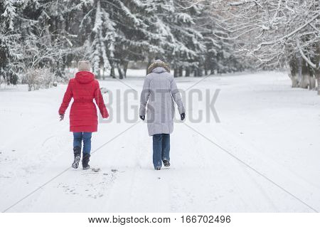DNEPR UKRAINE - DECEMBER 03 2016:Two women walking on an empty snowy street in Dnepr Ukraine at December 03 2016