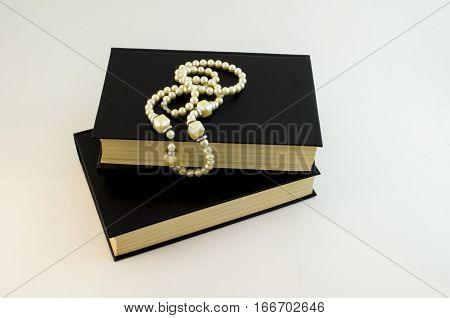 White pearls necklace on black. Books and pearls.